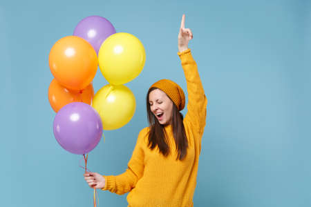 Funny young woman in sweater hat posing isolated on blue background. Birthday holiday party people emotions concept. Mock up copy space. Celebrating hold colorful air balloons point index finger up.