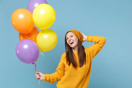 Cheerful young woman girl in sweater and hat posing isolated on blue background. Birthday holiday party people emotions concept. Mock up copy space. Celebrating hold colorful air balloons looking up. Imagens