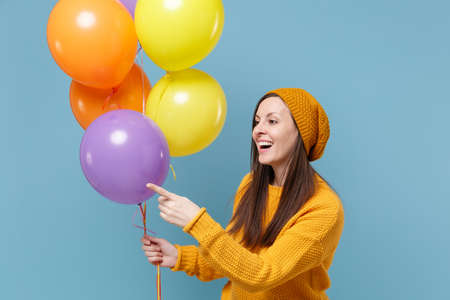 Cute young woman in sweater hat posing isolated on blue background. Birthday holiday party people emotions concept. Mock up copy space. Celebrating hold colorful air balloons point index finger aside.
