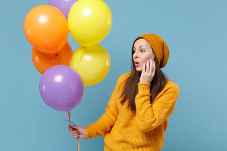Amazed young woman girl in sweater and hat posing isolated on blue background. Birthday holiday party people emotions concept. Mock up copy space. Celebrating hold colorful air balloons looking aside.