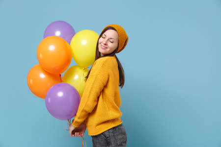Pretty young woman in sweater hat posing isolated on blue background. Birthday holiday party people emotions concept. Mock up copy space. Celebrating hold colorful air balloons keeping eyes closed. Imagens