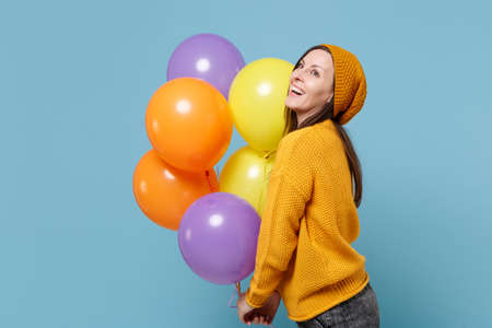 Laughing young woman girl in sweater and hat posing isolated on blue background. Birthday holiday party people emotions concept. Mock up copy space. Celebrating hold colorful air balloons looking up.