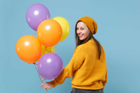 Back rear view of young woman in sweater hat posing isolated on blue background. Birthday holiday party people emotion concept. Mock up copy space. Celebrating hold colorful air balloons looking back. Imagens