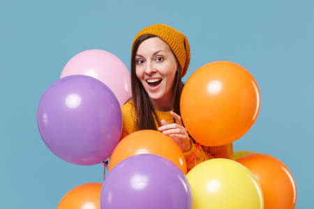 Excited young woman girl in sweater hat posing isolated on blue background studio portrait. Birthday holiday party, people emotions concept. Mock up copy space. Celebrating hold colorful air balloons.
