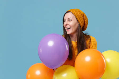 Laughing young woman girl in sweater hat posing isolated on blue background. Birthday holiday party, people emotions concept. Mock up copy space. Celebrating hold colorful air balloons looking aside. Imagens