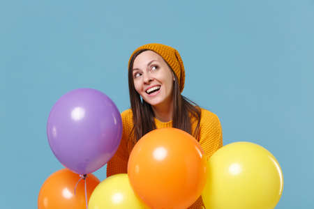Pensive young woman girl in sweater and hat posing isolated on blue background. Birthday holiday party, people emotions concept. Mock up copy space. Celebrating hold colorful air balloons looking up.