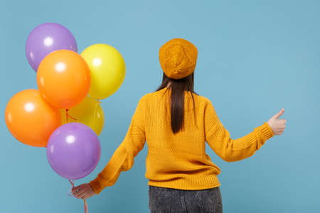 Back rear view of woman in sweater hat posing isolated on blue background. Birthday holiday party people emotions concept. Mock up copy space. Celebrating hold colorful air balloons showing thumb up. Imagens