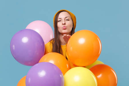 Young woman girl in sweater hat posing isolated on blue background. Birthday holiday party, people emotion concept. Mock up copy space. Celebrating hold colorful air balloons blowing sending air kiss. Imagens