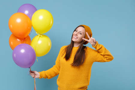 Smiling young woman in sweater hat posing isolated on blue background. Birthday holiday party people emotions concept. Mock up copy space. Celebrating hold colorful air balloons showing victory sign.