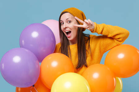 Young woman girl in sweater hat posing isolated on blue background. Birthday holiday party, people emotions concept. Mock up copy space. Celebrating hold colorful air balloons showing victory sign.