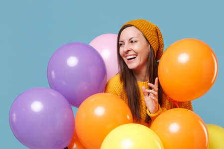 Cheerful young woman girl in sweater hat posing isolated on blue background. Birthday holiday party, people emotions concept. Mock up copy space. Celebrating hold colorful air balloons looking aside. Imagens