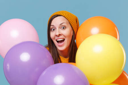 Surprised young woman girl in sweater hat posing isolated on blue background studio portrait. Birthday holiday party people emotion concept. Mock up copy space. Celebrating hold colorful air balloons.