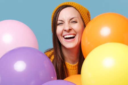 Laughing young woman girl in sweater hat posing isolated on blue background studio portrait. Birthday holiday party people emotion concept. Mock up copy space. Celebrating hold colorful air balloons.