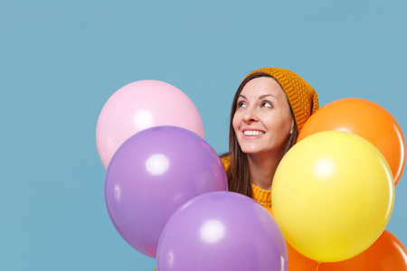 Pretty young woman girl in sweater and hat posing isolated on blue background. Birthday holiday party, people emotions concept. Mock up copy space. Celebrating hold colorful air balloons looking up.
