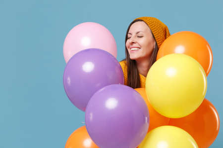 Cute young woman girl in sweater hat posing isolated on blue background. Birthday holiday party people emotions concept. Mock up copy space. Celebrating hold colorful air balloons keeping eyes closed.