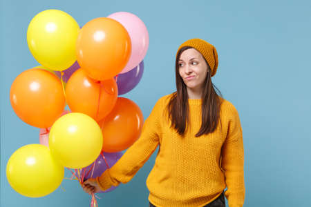Dissatisfied young woman girl in sweater and hat posing isolated on blue background in studio. Birthday holiday party people emotion concept. Mock up copy space. Celebrating hold colorful air balloon.