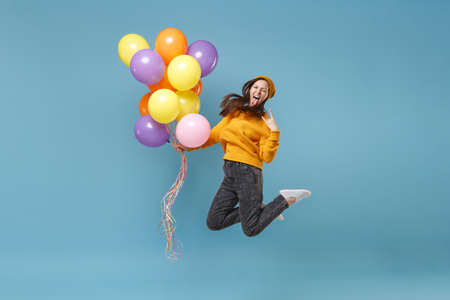 Surprised woman in sweater hat posing isolated on blue background. Birthday holiday party, people emotions concept. Mock up copy space. Celebrating hold air balloons jumping showing horns up gesture.