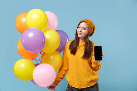 Smiling woman in sweater hat posing isolated on blue background. Birthday holiday party people emotions concept. Mock up copy space. Celebrating hold air balloons mobile phone with blank empty screen.