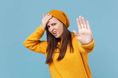 Dissatisfied young woman girl in yellow sweater hat posing isolated on blue background studio portrait. People lifestyle concept. Mock up copy space. Showing stop gesture with palm, put hand on head.