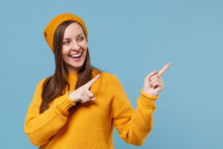 Funny young brunette woman girl in yellow sweater hat posing isolated on blue background studio portrait. People sincere emotions lifestyle concept. Mock up copy space. Pointing index fingers aside.