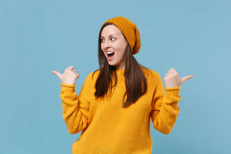 Cheerful young brunette woman girl in yellow sweater and hat posing isolated on blue background studio portrait. People sincere emotions lifestyle concept. Mock up copy space. Pointing thumbs aside.
