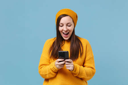 Excited young brunette woman girl in yellow sweater and hat posing isolated on blue background studio portrait. People lifestyle concept. Mock up copy space. Using mobile phone, typing sms message.