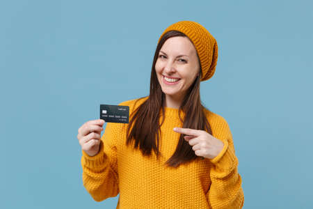 Smiling young woman in yellow sweater and hat posing isolated on blue background studio portrait. People sincere emotions lifestyle concept. Mock up copy space. Point index finger on credit bank card.