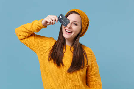 Funny young woman in yellow sweater and hat posing isolated on blue wall background studio portrait. People sincere emotions lifestyle concept. Mock up copy space. Covering eye with credit bank card. Reklamní fotografie