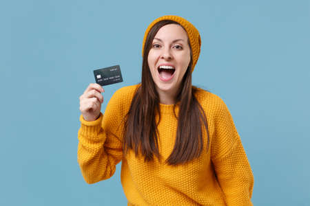 Cheerful young brunette woman girl in yellow sweater and hat posing isolated on blue background studio portrait. People sincere emotions lifestyle concept. Mock up copy space. Hold credit bank card.