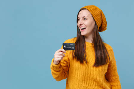 Cheerful young woman in yellow sweater hat posing isolated on blue wall background studio portrait. People sincere emotions lifestyle concept. Mock up copy space. Looking aside hold credit bank card.