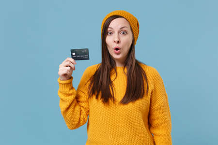 Shocked young brunette woman girl in yellow sweater and hat posing isolated on blue background studio portrait. People sincere emotions lifestyle concept. Mock up copy space. Hold credit bank card. Reklamní fotografie