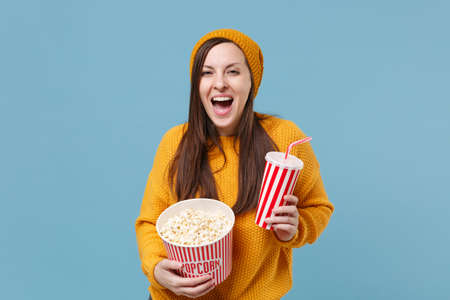Funny young brunette woman in sweater hat posing isolated on blue background. People emotions in cinema lifestyle concept. Mock up copy space. Watching movie film hold bucket of popcorn cup of soda.