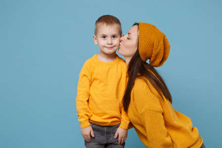 Woman in yellow clothes kissing kiss cheek cute child baby boy 4-5 years old. Mommy little kid son isolated on blue background studio portrait. Mothers Day love family parenthood childhood concept.