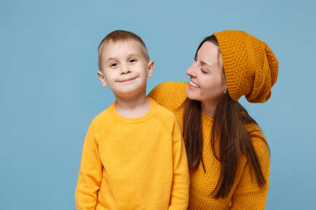 Woman in yellow clothes have fun posing with cute child baby boy 4-5 years old. Mommy little kid son isolated on blue background studio portrait. Mothers Day love family parenthood childhood concept.