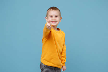 Little cute kid boy 4-5 years old wearing yellow clothes isolated on pastel blue wall background, children studio portrait. People sincere emotions, childhood lifestyle concept. Mock up copy space.