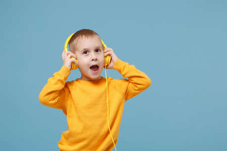 Little cute kid boy 4-5 years old wearing yellow clothes listen music in headphones isolated on pastel blue background, children studio portrait. People sincere emotions, childhood lifestyle concept.