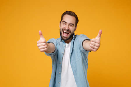 Cheerful young bearded man in casual blue shirt posing isolated on yellow orange wall background studio portrait. People sincere emotions lifestyle concept. Mock up copy space. Showing thumbs up.