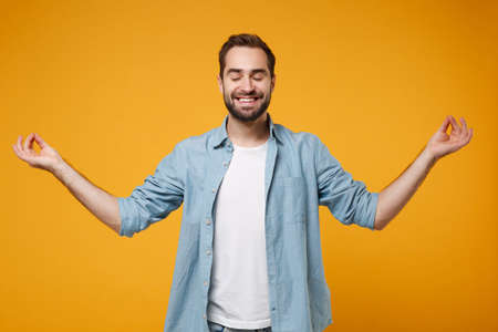 Smiling young bearded man in blue shirt posing isolated on yellow orange background. People lifestyle concept. Mock up copy space. Hold hands in yoga gesture, relaxing meditating, keeping eyes closed. Stock Photo
