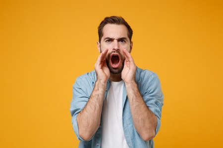 Young bearded man in casual blue shirt posing isolated on yellow orange wall background, studio portrait. People emotions lifestyle concept. Mock up copy space. Screaming with hand gesture near mouth. Stockfoto
