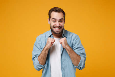Smiling young bearded man in casual blue shirt posing isolated on yellow orange background, studio portrait. People lifestyle concept. Mock up copy space. Clenching fists, waiting for special moment.