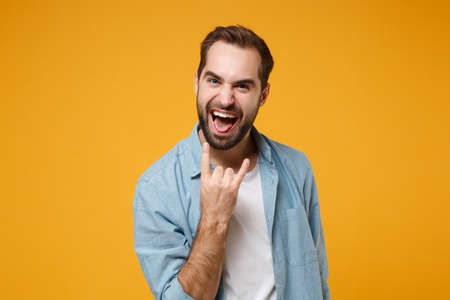 Crazy young bearded man in casual blue shirt posing isolated on yellow orange background studio portrait. People lifestyle concept. Mock up copy space. Showing horns up gesture, heavy metal rock sign.