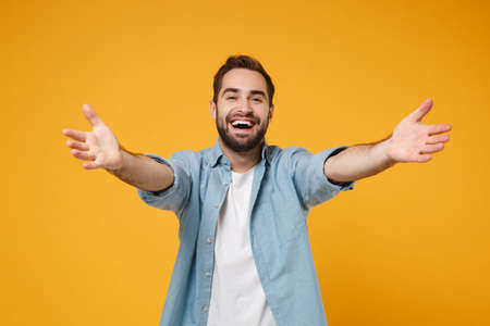 Cheerful young bearded man in casual blue shirt posing isolated on yellow orange background studio portrait. People emotions lifestyle concept. Mock up copy space. Standing with outstretched hands.