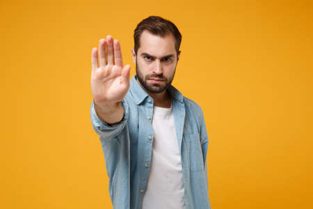 Serious young bearded man in casual blue shirt posing isolated on yellow orange wall background, studio portrait. People emotions lifestyle concept. Mock up copy space. Showing stop gesture with palm. Stock Photo