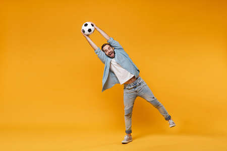 Funny young man in casual blue shirt posing isolated on yellow orange wall background, studio portrait. People sincere emotions lifestyle concept. Mock up copy space. Catching soccer ball in air.