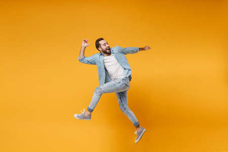 Side view of cheerful young bearded man in casual blue shirt posing isolated on yellow orange background, studio portrait. People emotions lifestyle concept. Mock up copy space. Jumping looking back.