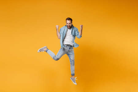 Joyful young bearded man in casual blue shirt posing isolated on yellow orange background, studio portrait. People sincere emotions lifestyle concept. Mock up copy space. Jumping doing winner gesture.