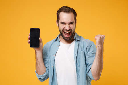 Joyful young man in blue shirt posing isolated on yellow orange background. People lifestyle concept. Mock up copy space. Holding mobile phone with blank empty screen, doing winner gesture, screaming.