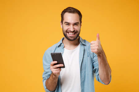 Smiling young man in casual blue shirt posing isolated on yellow orange wall background in studio. People lifestyle concept. Mock up copy space. Using mobile phone typing sms message showing thumb up. Banque d'images