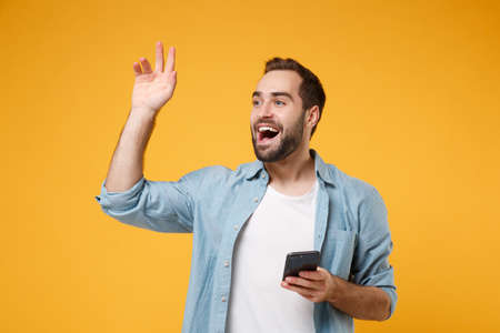 Cheerful young man in casual blue shirt posing isolated on yellow orange background. People lifestyle concept. Mock up copy space. Hold mobile phone, waving and greeting with hand as notices someone.