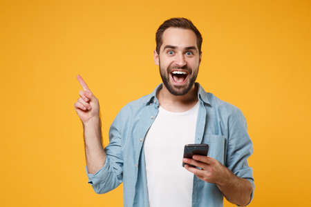 Excited young man in casual blue shirt posing isolated on yellow orange background. People lifestyle concept. Mock up copy space. Using mobile phone, typing sms message pointing index finger aside up.